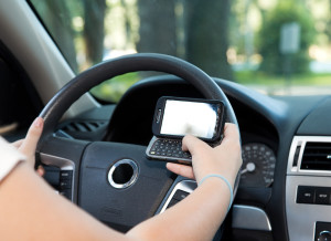 Closeup of a smart phone with a female hand texting and driving.